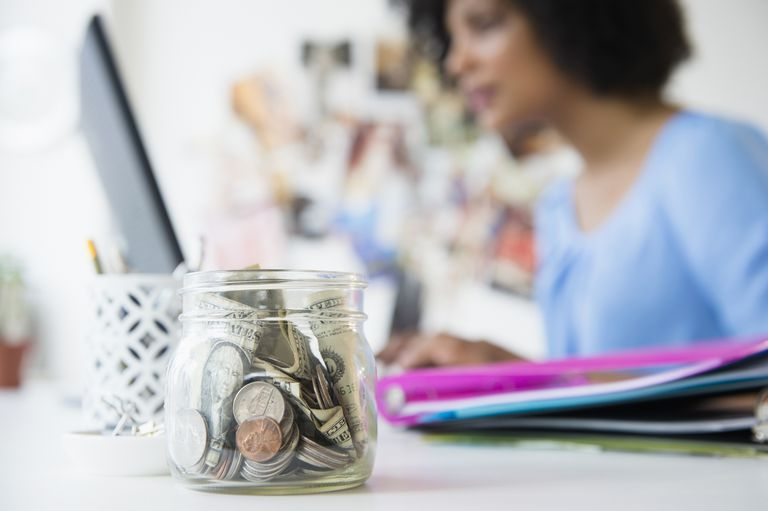 Woman on computer with jar of money in foreground