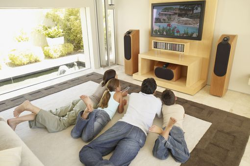 Family of four lying on floor watching television