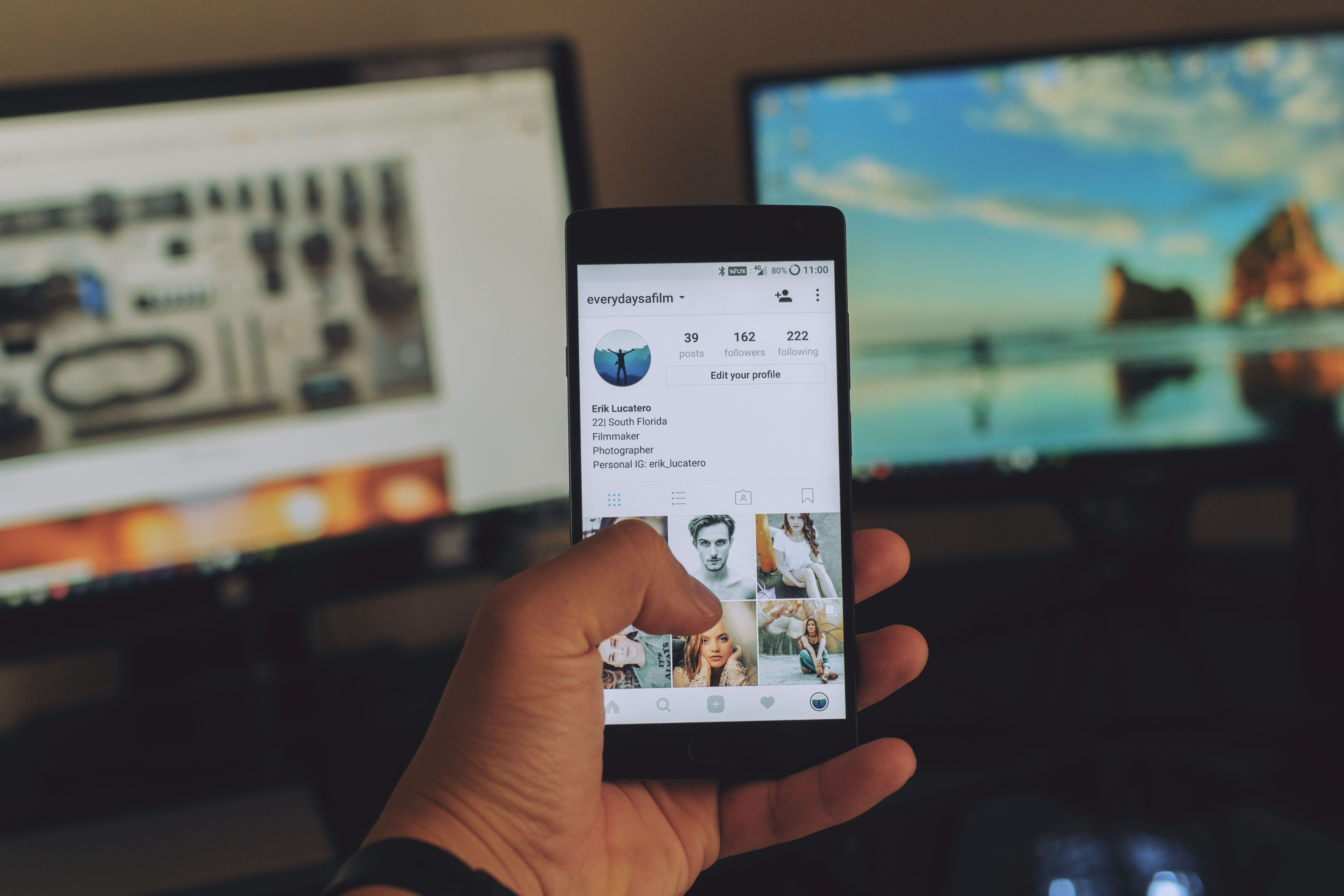 A person holding up a smartphone showing an Instagram profile