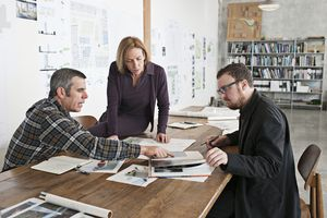 Three designers in meeting gathered around a table