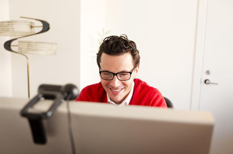 Man Smiling While Using Computer