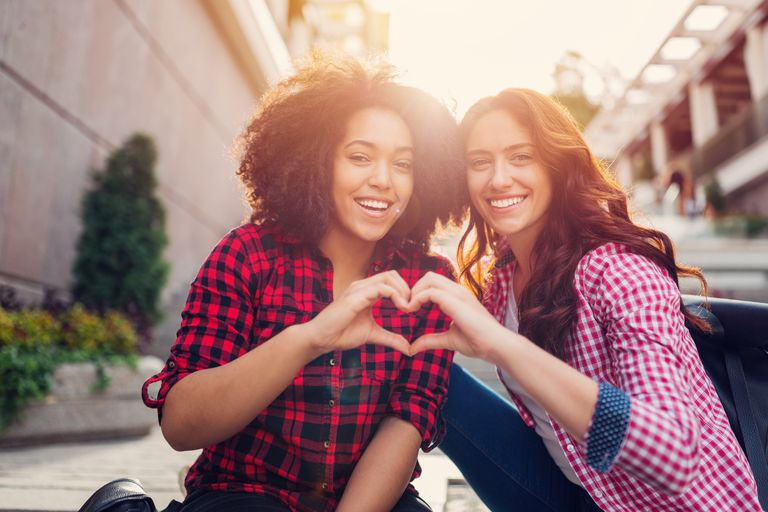 Two female friends showing a heart symbol with their hands.