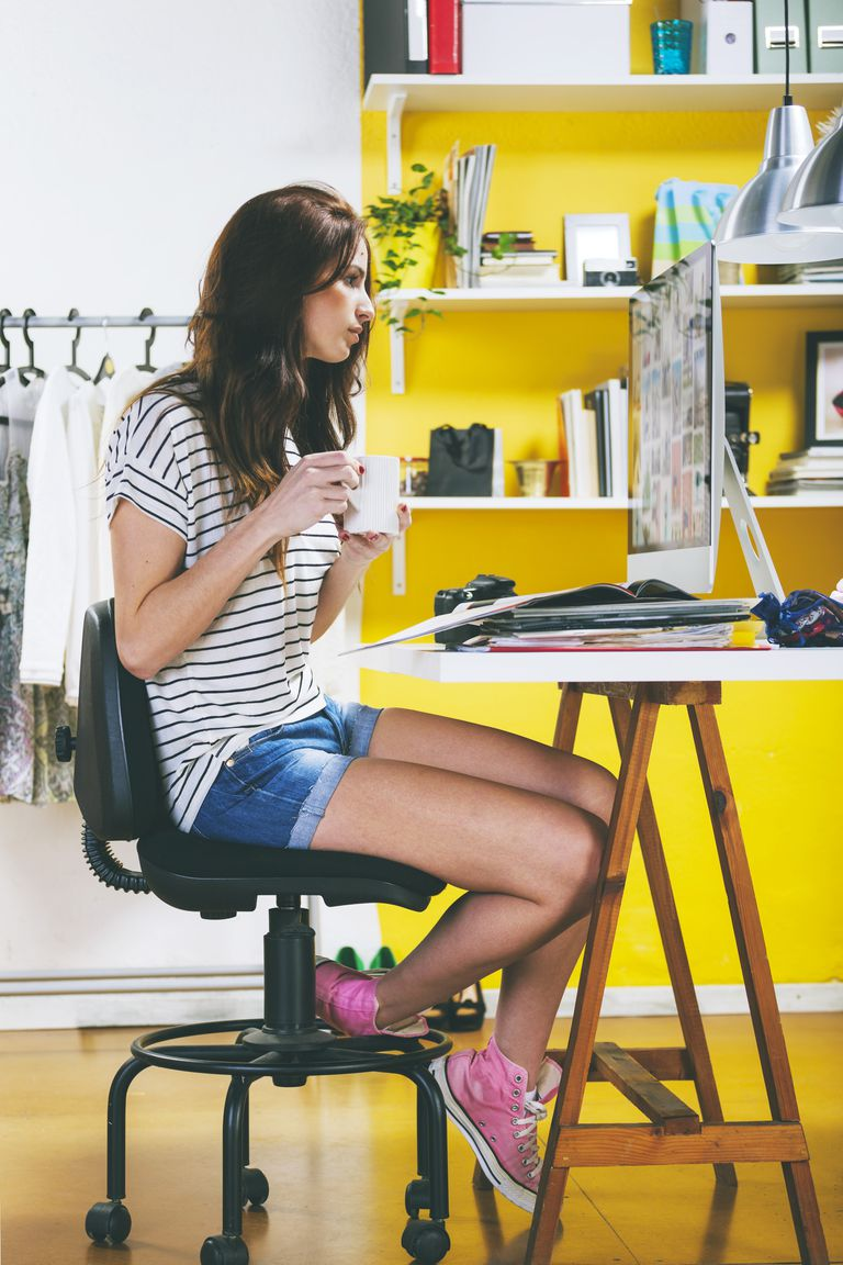 Young woman designer holding coffee cup looking at computer screen