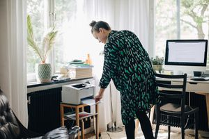 Woman using a printer in what appears to be a home office.