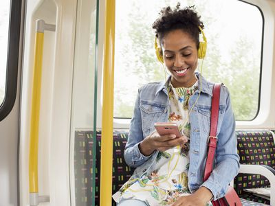 A woman sitting on public transport smiling at her smartphone with headphones on
