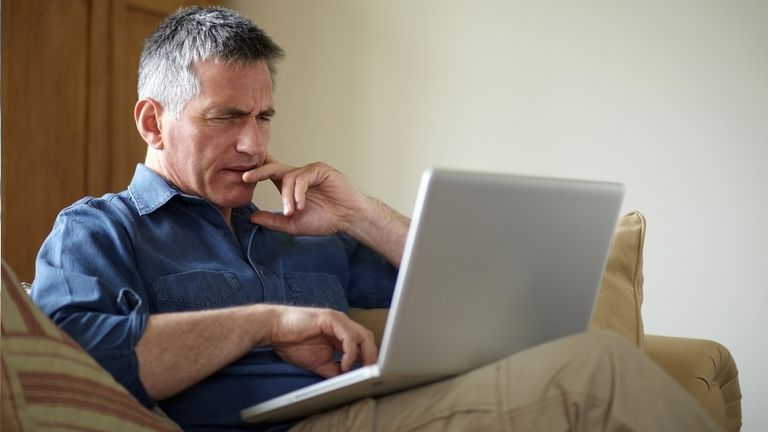 Middle-aged man looking confused with a laptop while thinking about Windows as a Service.