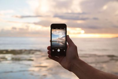 Mobile phone taking picture of sunset on the beach