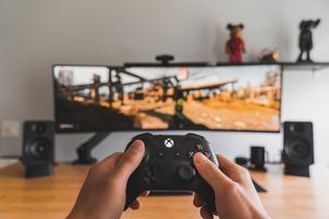 Someone gaming on a large, curved screen, holding an Xbox controller.
