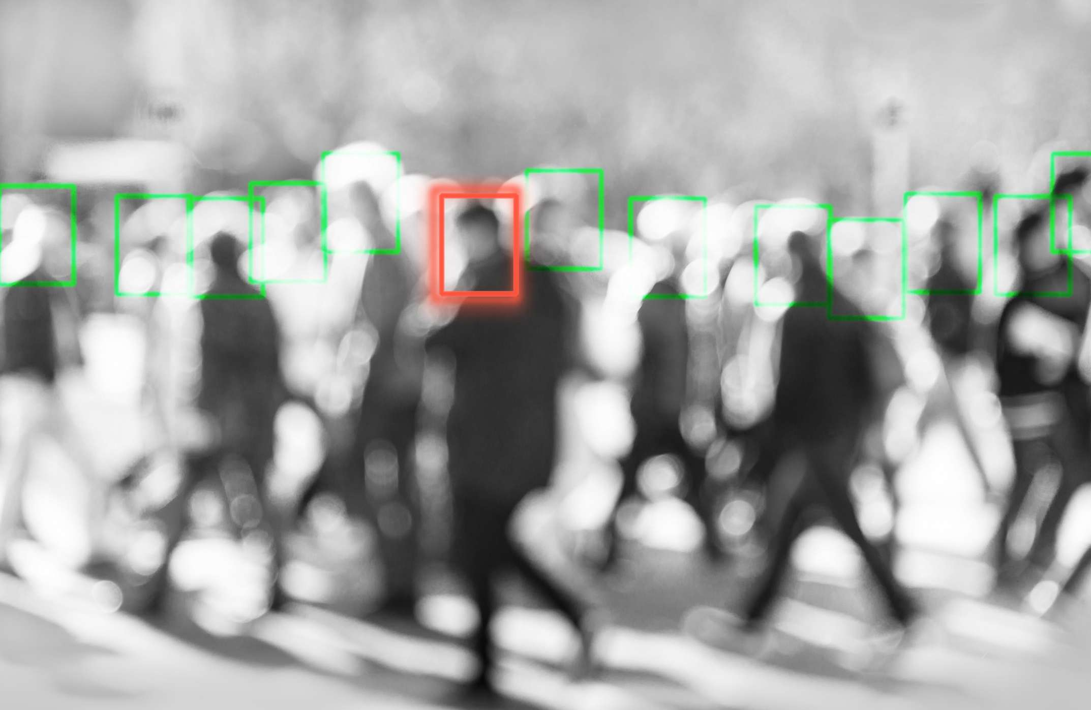 Tracking people in a crowd with one person called out by a red outline.