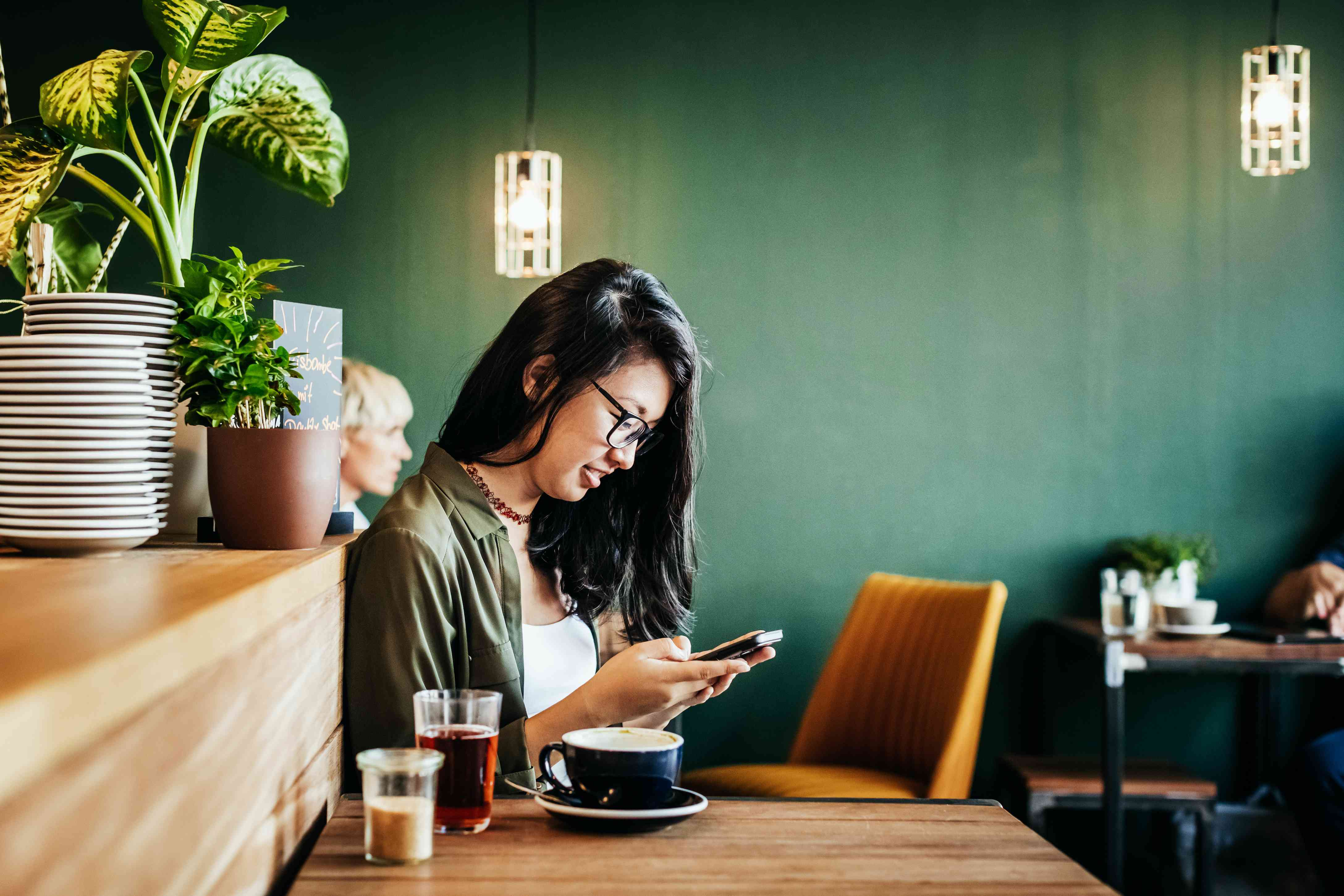 A woman using a phone in a coffee shop.