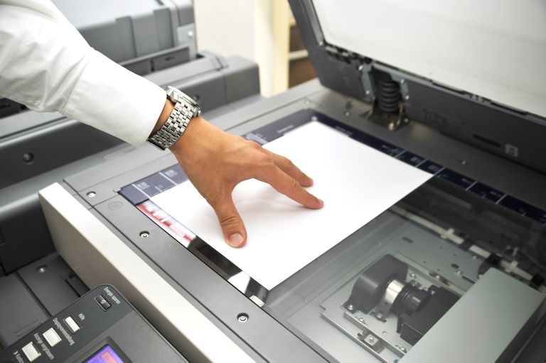 Photograph of man's left hand holding a sheet of paper face down on a flatbed scanner.