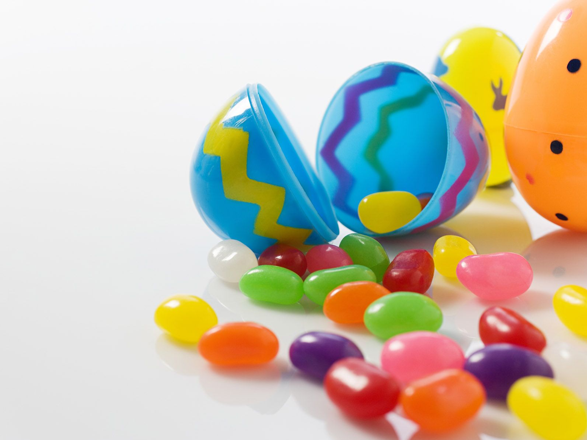 Free Easter wallpaper featuring colorful plastic Easter eggs and jellybeans