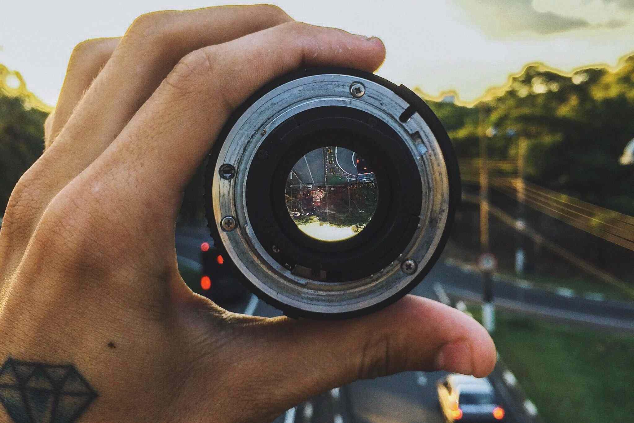 Hand holding camera lens/