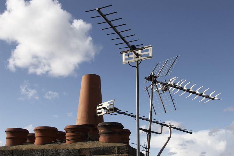 Television aerials and chimney pots with blue sky