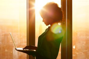A woman with an open laptop in front of a bright window