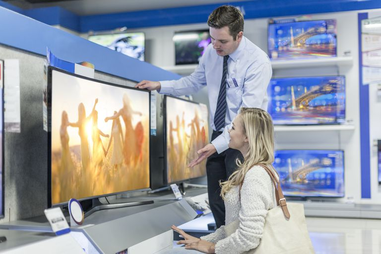 Shop assistant showing flatscreen TV to customer deciding on a new TV purchase