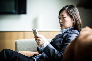 woman using smartphone on couch