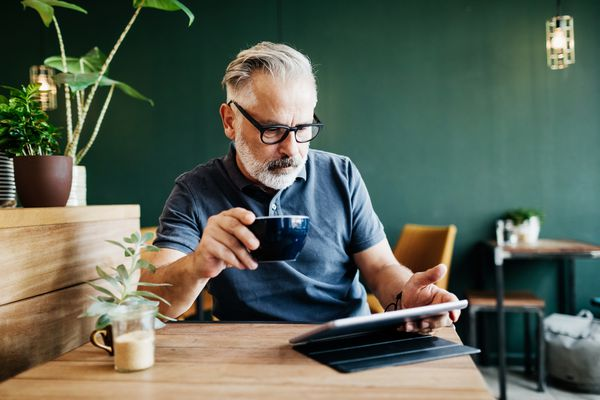 A mature adult using an iPad and drinking coffee.