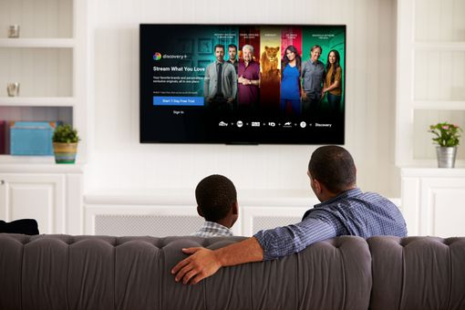 A man and boy watch Discovery Plus on Fire TV.