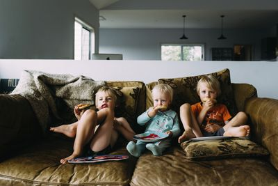 Three young children sitting on a sofa watching TV