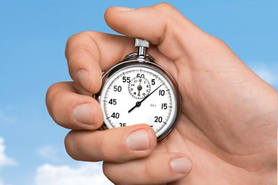 A hand holding a stopwatch