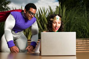 A man and woman dressed up as superheroes reading comic books online on their computer.