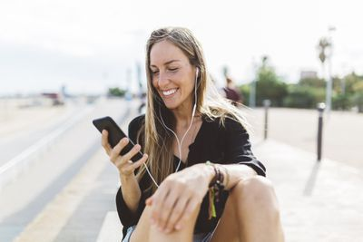 Smiling young woman with cell phone and earbuds on waterfront promenade