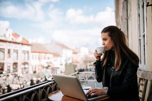 A woman sitting on a balcony sipping coffee with a laptop in front of her