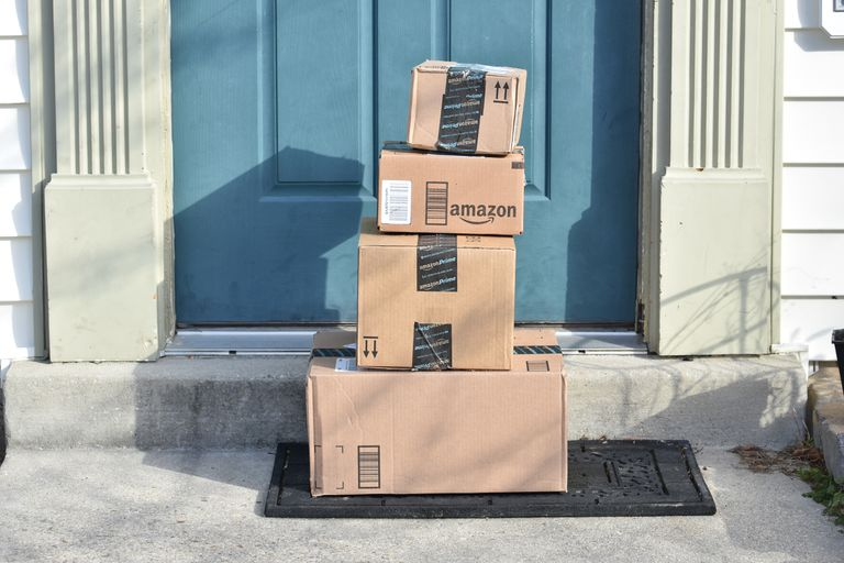 Tower of Amazon packages at blue house door