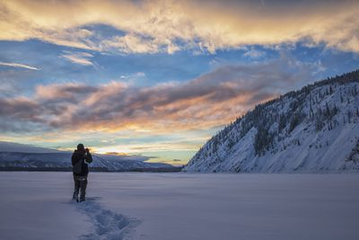 Photographer taking a landscape under snowy mountains