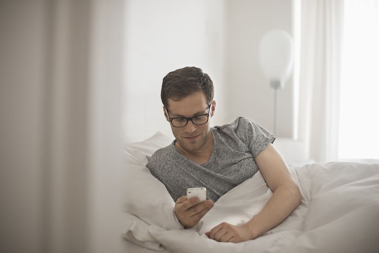 A man lying in bed checking his messages on his phone.
