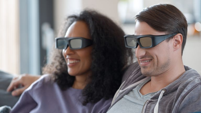 Young couple watching TV in 3D