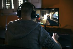 A man with his back to the camera wearing headphones and looking at a PC monitor