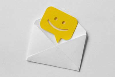 Email envelope with smiling message bubble on white background