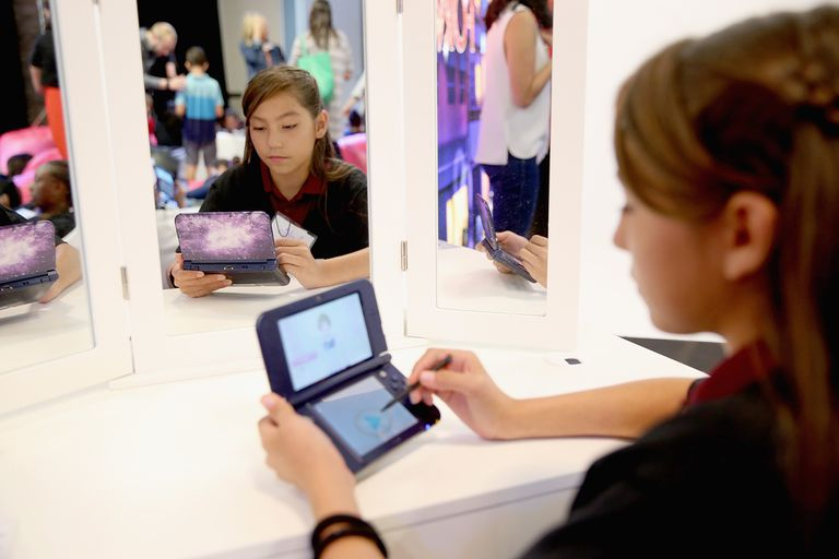 Young woman playing with a Nintendo device in front of mirrors