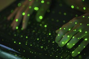 Close-up of green lights over cropped hands using laptop keyboard