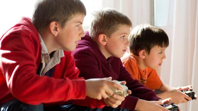 Three brothers playing video games on their Xbox One console with family settings enabled.