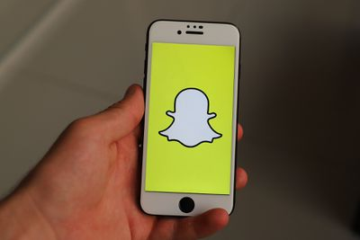 An image of the Snapchat ghost icon on a smartphone screen