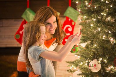 Parent and child decorating a tree