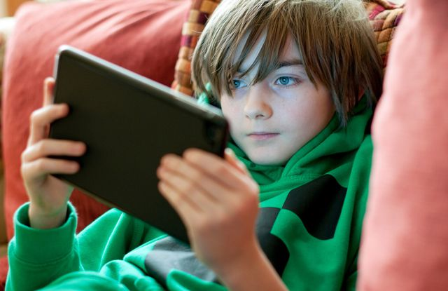 Young kid playing game on iPad