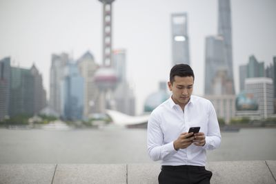Businessman using phone with Shanghai cityscape : Stock Photo View similar imagesMore from this photographerDownload comp Businessman using phone with Shanghai cityscape