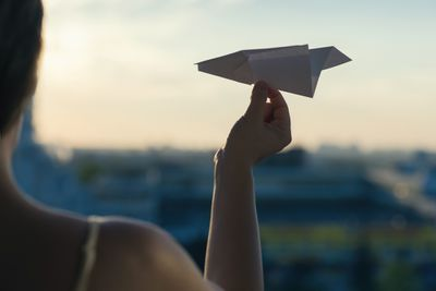 Someone launching a paper airplane from a window to symbolize sending a Telegram message.
