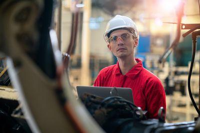 An engineer watching a welding robot.