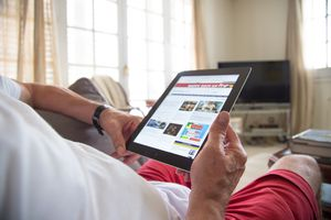 Photo of a man reading an iPad.