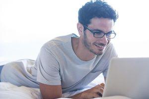 Smiling man using laptop in bed