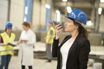 Woman in hard hat talking into phone at work site