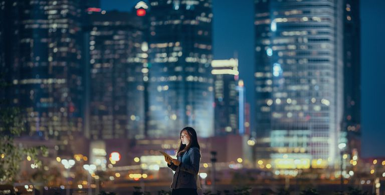 Woman using tablet while standing in front of several skyscrapers