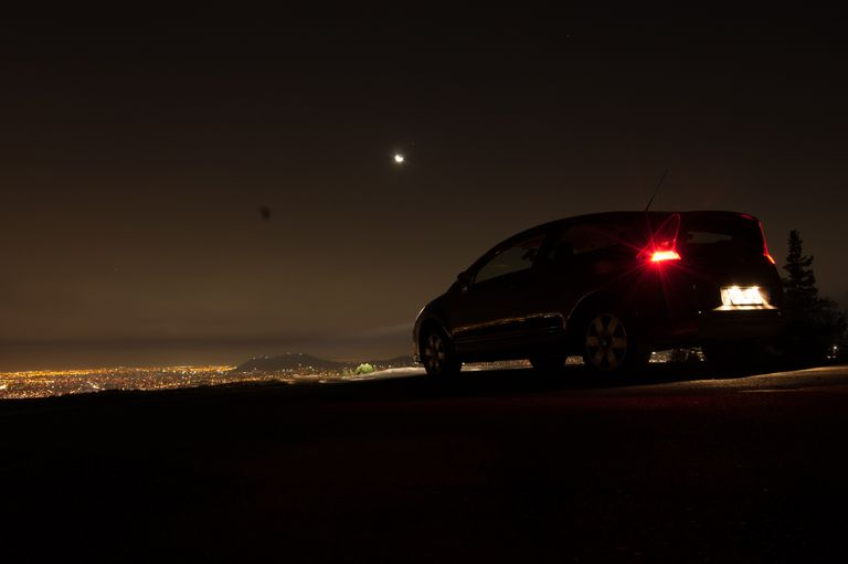 A Car On Hill Overlooking City At Night