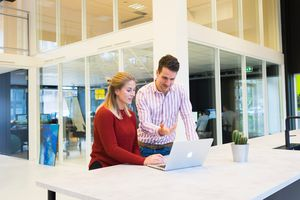 Coworkers at laptop learning how to add eye-catching backgrounds to PowerPoint
