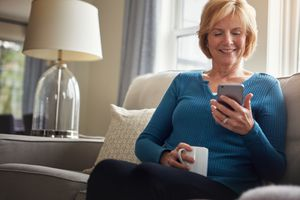 A woman is sitting on a sofa and looking at a mobile phone.